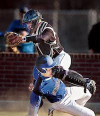 Burleson Centennial baserunner Nate Menchaca takes a knee to the face as he is forced out at home plate by Denton catcher Dylan Tekell in February at Bronco Field.Al Key - DRC file photo
