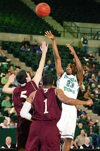 North Texas sophomore guard Jordan Williams, right, takes a shot over Louisiana-Monroe's Trent Mackey, left, and Jayon James on Saturday night at the Super Pit.DRC/David Minton