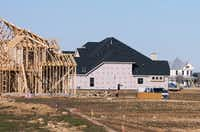 New homes under construction contrast with a renovated farmhouse being used as a hospitality center and office at the center of the Harvest development off FM407 near Northlake.David Minton