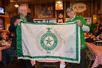 Outgoing University of North Texas President Lane Rawlins, left, hands over the presidential flag to incoming president Neal Smatresk. The two had a friendly dinner together Friday.Jenna Duncan - DRC