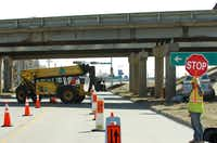 Construction crews work Friday on the expansion of the Interstate 35E overpass over Bonnie Brae Street in Denton.Al Key - DRC