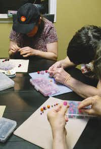 April, Elaine and Brenda, residents of the Denton State Supported Living Center, make bracelets at Impressions on Wednesday.DRC/David Minton