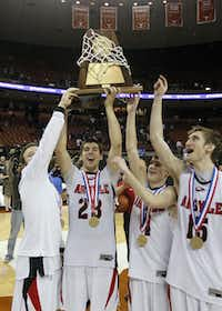 Argyle senior Clarke Overlander, second from left, holds the Class 3A trophy as he celebrates with teammates March 10 in Austin.DMN file photo