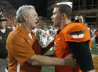 Texas coach Mack Brown, left, talks with Oklahoma State quarterback J.W. Walsh following the Longhorns' win Saturday in Stillwater, Okla.AP/Sue Ogrocki