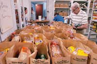 Gene Williams — at age 94, the oldest volunteer at the Denton Community Food Center — adds canned items to bags of food to distribute Wednesday for the Thanksgiving holiday.David Minton - DRC