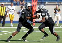 Guyer quarterback Jerrod Heard, left, hands the ball off to Richard Whitaker on Saturday in Midland.Telegram/James Durbin