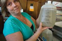 In 2012, business owner Cindy Brown holds a jug of smelly, murky water saved from May 2012 when the town of Robert Lee ran out of water.G. Morty Ortega - For the DRC