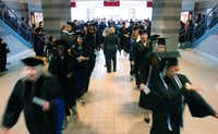 Graduates flow down the stairs and through the lobby of Pioneer Hall on their way to the Texas Woman's University commencement ceremony on Friday at Kitty Magee Arena in Denton.David Minton - DRC