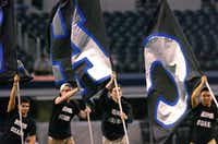 "The Guyer Honor Guard runs the ""CATS"" flags across the field after a touchdown Friday against San Antonio Northside Brennan in Arlington.David Minton - DRC"