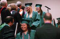 Fred Moore High School graduates cross the stage to receive their diplomas at Thursday's commencement ceremony at the University of North Texas Gateway Center.David Minton - DRC