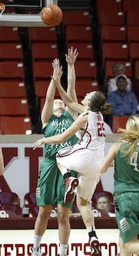 Oklahoma guard Whitney Hand, center, shoots as North Texas forward Sara Stanley, left, defends Dec. 6 in Norman, Okla. Hand, a Liberty Christian product, injured her knee on the play.Associated Press/Sue Ogrocki