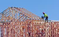 A construction worker uses a nail gun on a roof truss at the site of an apartment complex being built on the southwestern corner of the intersection of Loop 288 and North Locust Street on Nov. 3.Al Key - DRC file photo