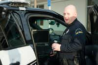 Lake Dallas Police Chief Dan Carolla demonstrates the features of a fully equipped police vehicle for city council members.DRC