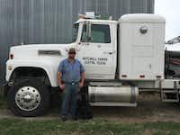 Travis Mitchell poses with the family dog, Doc, in front of the family farm truck. Mitchell and his family, who are tenant farmers and have no ownership over the land they lease, are losing valuable farming land to housing developments that are eagerly and rapidly building on the Justin area's untouched and vast acres of land.For the DRC/Lauren Rosenthal