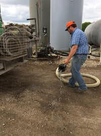 Travis Mitchell removes the nozzle from the truck, spilling a little fertilizer. The job of a farmer involves mundane but strenuous work.For the DRC/Lauren Rosenthal