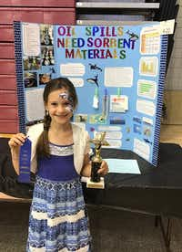 Denton Calvary Academy fourth-grader Jordan Lassiter shows off her prize after she received a perfect score at the Texas Woman's University Science Fair for her project that demonstrated the effects of ocean oil spills on marine life.Courtesy Denton Calvary Academy