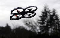 In this March 14, 2015 file photo, a radio-controlled drone appears in flight during an International Drone Day event at an elementary school in Roseburg, Ore.AP