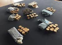 "The 913 gold coins which were found in a piano, are displayed at Ludlow Museum  in Ludlow, England  Thursday April 20, 2017, where they are being kept under lock and key. As a mystery surrounds the identity of the rightful heirs to a treasure trove of gold coins. British officials say they have been unable to trace the rightful heirs to a trove of gold coins  worth a ""life-changing"" amount of money. The school that owns the piano and the tuner who found the gold are now in line for a windfall after a coroner investigating the find declared it treasure. (Richard Vernalls/PA via AP)AP"