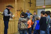 """Jamie McClain, associate pastor of Denton County Cowboy Church in Ponder, delivers a special """"kids' sermon"""" to children in simple language and story form before the adult sermon begins and the children move to another room.Sarah Sarder/For the DRC"""