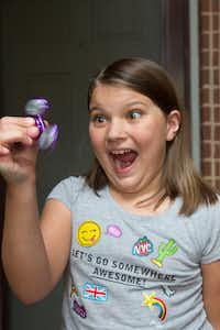 Marlena Flores, a third grader at Ryan Elementary School, loves her fidget spinner. The spinner is a popular new toy. The spinner has at least three small arms that revolve around a bearing. A flick of the finger sets the device to spinning with the speed of a top. Some teachers hate the spinners, others say the toys help students focus and soothe students with anxiety or autism. , Tuesday, May 16, 2017, in Denton, Texas, Jeff Woo/DRCDRC