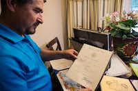 Hugo Ramirez of Oak Point looks at an award he received from the U.S. Navy for good conduct during his time in the service.DRC