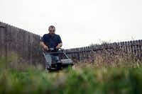 Hugo Ramirez cuts grass at a house where the renters paid him $200. Ramirez, who was laid off from his job at Peterbilt, works temporary warehouse jobs and other odds jobs just to make ends meet.DRC