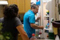 Hugo Ramirez opens the refridgerator door at his home as he talks to his partner, Alicia Vazquez.DRC