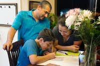 Hugo Ramirez, left, and Alicia Vazquez help their son, Jesus Curiel, with a homework assignment.DRC