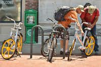 Locals take a closer look at a VBike near the Courthouse on the Square in downtown Denton.  VBikes are a new bike-sharing service that launched in Denton this weekDRC
