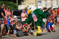 University of North Texas mascot Scrappy high-fives kids in Denton's Yankee Doodle Parade in 2014.DRC file photo