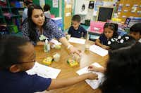 Laura Koenig, (adult) pre-k teacher, is shown in 2015  teaching Myriah Love, (left to right) Jayden Murillo, Denise Alamilla and Edgar Sandate  how math a game works in class at Cesar Chavez Learning Center in Dallas.Staff Photographer