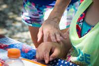 Angela Biggs shows affection towards her daughter Amber Reynolds by touching her hand during a picnic at Buffalo Valley Event Center. DRC