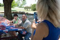 Amber Reynolds, left, sits next to her father, Tony Reynolds, as her mother, Angela Biggs, snaps a photo of them during a picnic at Buffalo Valley Event Center. DRC
