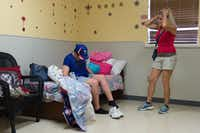 Amber Reynolds, left, puts on shoes in her room as her mother, Angela Biggs, waits for her to get ready so they can leave for the park.DRC