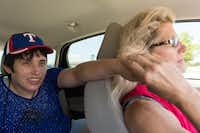 Amber Reynolds reaches out for her mother's hand during a car ride back to the Denton State Supported Living Center. Angela Biggs, who lives 135 miles away in Waco, will drop off her daughter at the center, then drive to a relative's place to spend the night. DRC
