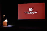 Carine Feyten, chancellor and president of Texas Woman's University, unveils the new logo for the university Monday at Margo Jones Performance Hall.DRC