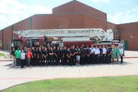 Lake Dallas administrators and students hop on their new fire engine donated by the Lake Cities Fire Department. Students enrolled in the district's fire academy will use the engine during their classes.Courtesy Photo