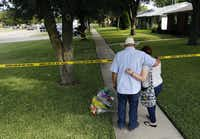 Hal Moss and his daughter Kelsey Moss, who knew several of the eight friends shot to death Sunday at a party in Plano, place flowers and say a prayer for the dead on Tuesday.The Dallas Morning News