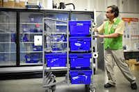 Wille Pierson, who has worked at WalMart for 11 months, rolls his cart of bins to the other side of the room after he finishes preparing a customer's order for pick-up at the WalMart Neighborhood Market.DRC
