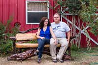 Sue Newhouse and Brian O'Dwyer of Aunt Sue's Barn sit on a custom locally made bench in front of their red barn.DRC