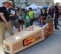 "Wendy Haun (driver) and Jake Laughlin (coffin pusher) head for the starting line in the Discover Denton coffin to compete in the 2016 Day of the Dead Coffin Races in downtown Denton.<p><span style=""font-size: 1em; background-color: transparent;"">Denton Convention & Visitors Bureau</span></p>"