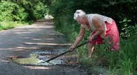 This Dallas Morning News photo from 1997 captures an 80-year-old Olive Stephens working on a pothole in Shady Shores. She always kept a pair of  gloves, tools and a shovel in the back of her car.The Dallas Morning News