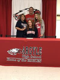 Argyle senior Gabby Standifer (seated in middle) smiles during her signing ceremony as she takes a picture with her family. Standifer is going into her third year at Argyle and just signed with Division I Fresno State.Courtesy Photo