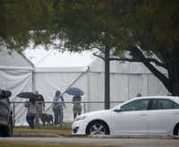 People arrive for Sunday's memorial service in Sutherland Springs, held inside a massive tent at a baseball field.The Dallas Morning News