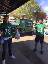 Lake Dallas High School football players Hayden Brockenbush, left, and DL Roberson pass out turkeys to community members. The players teamed up with local businesses to hand out food that families in need can prepare on Thanksgiving.Darryl Minor