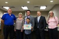 Ginnings Elementary fourth-grader Luis Hernandez shows off his prize-winning artwork with Denton ISD teachers and administrators at the Young Artists Night at UMB Bank. Hernandez won first place for his grade level in the annual Adopt-A-School Art Contest and received a Michael's gift card.Denton ISD