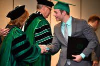 University of North Texas graduate Matt Rewis shakes hands after receiving his diploma Friday, Dec. 15, 2017, in New Orleans. UNT had a small commencement ceremony for eight graduates at the Hilton New Orleans Riverside.Michael Clements