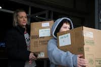 Ten-year-old Kai Goree, right, and his mother Charity, left, carry boxes of prepared meals to their car for delivery to the Little Elm Police Department.DRC
