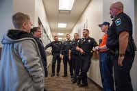Ten-year-old Kai Goree, left, speaks with members of the Little Elm Police Department and Fire Department after delivering their meals.DRC