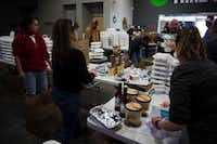 Volunteers organize stacks of prepared lunches into boxes for delivery to first responders.DRC